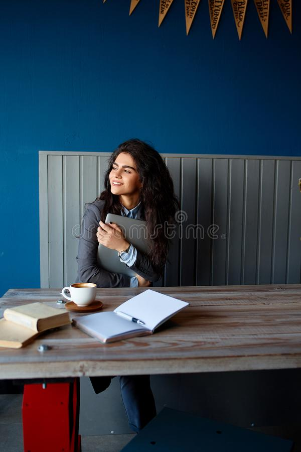 Beautiful brunette sitting in coffee shop and working on computer. Beautiful brunette sitting in coffee shop and working on computer stock photo