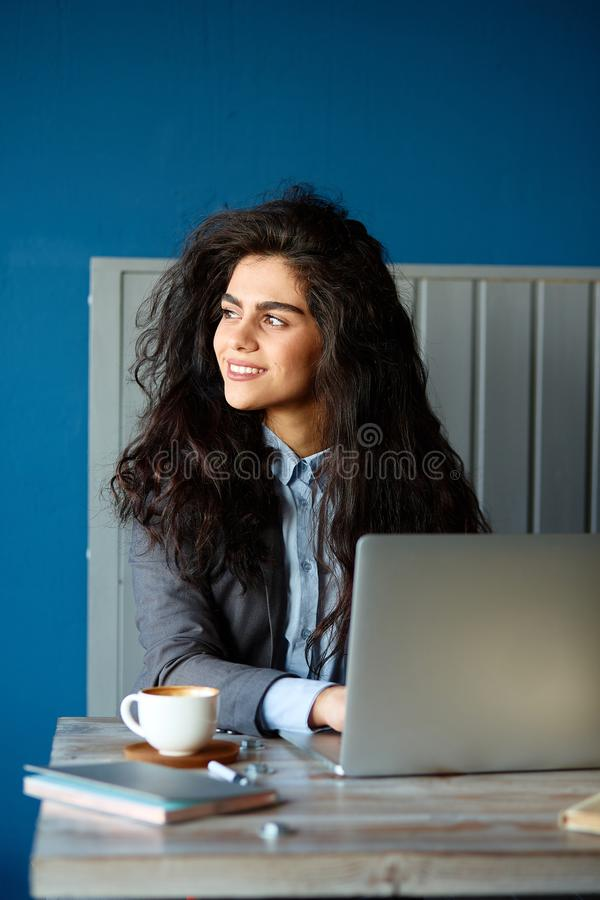 Beautiful brunette sitting in coffee shop and working on computer. Beautiful brunette sitting in coffee shop and working on computer stock photography