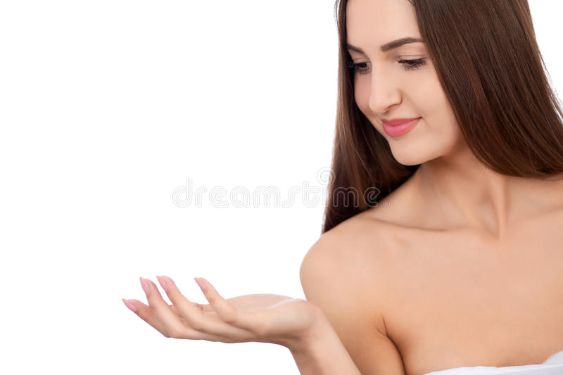 Beautiful Brunette Spa Girl showing empty copy space on the open hand palm for text. Proposing a product. Gestures for. Beauty Spa Woman with perfect skin royalty free stock photos