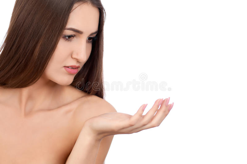 Beautiful Brunette Spa Girl showing empty copy space on the open hand palm for text. Proposing a product. Gestures for. Beauty Spa Woman with perfect skin royalty free stock photo