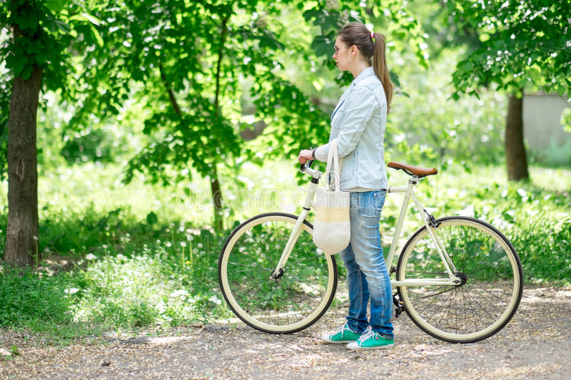 Beautiful brunette standing near her yellow bicycle royalty free stock image
