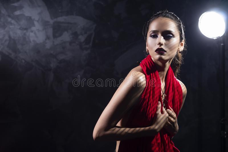 Beautiful brunette topless girl model, covering her naked breast. With a red scarf and wearing a modern necklace on the deep decollete. Copy space. Advertising royalty free stock images