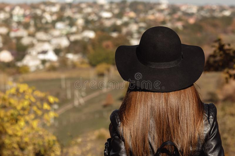 Woman with backpack is looking at the city in autumn day royalty free stock photo