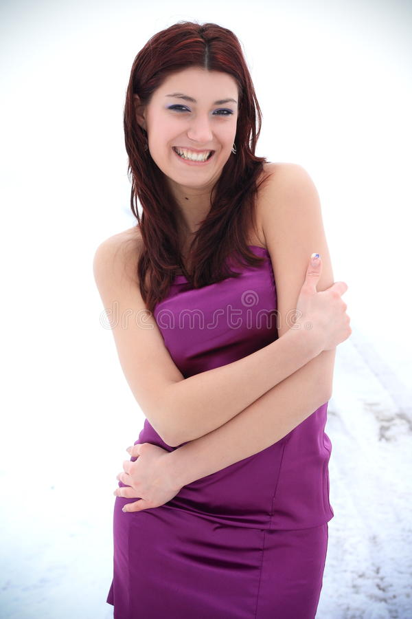 Beautiful brunette in a winter nature. Beautiful brunette in a purple evening dress posing in a winter nature, fashion photography stock photo