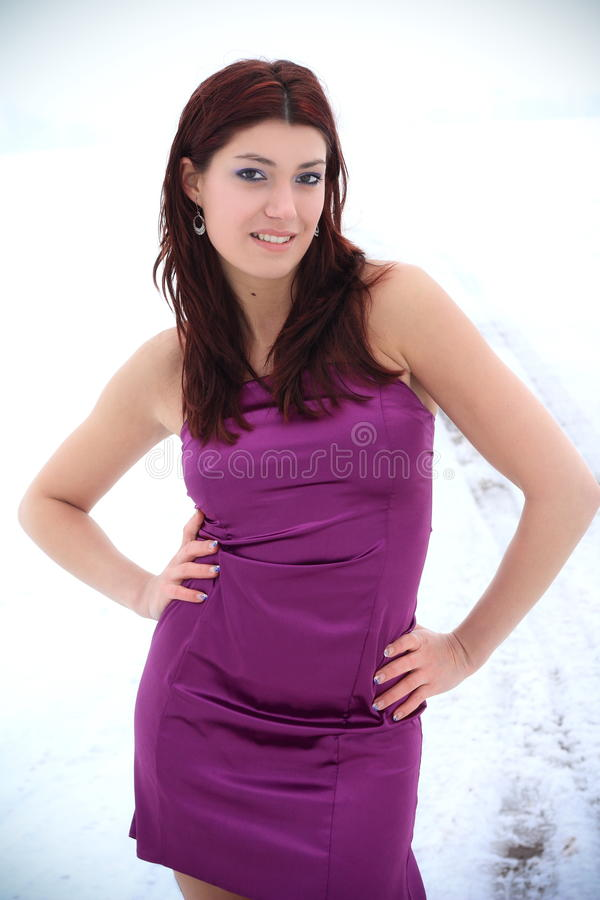 Beautiful brunette in a winter nature. Beautiful brunette in a purple evening dress posing in a winter nature, fashion photography royalty free stock images