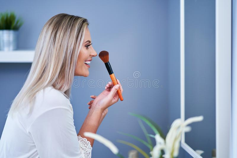 Beautiful brunette woman applying make-up in the bathroom. Picture of adult brunette woman in the bathroom stock photography