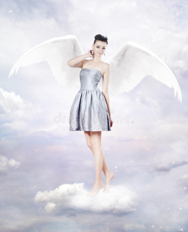 Beautiful brunette woman as angel in heaven royalty free stock photography