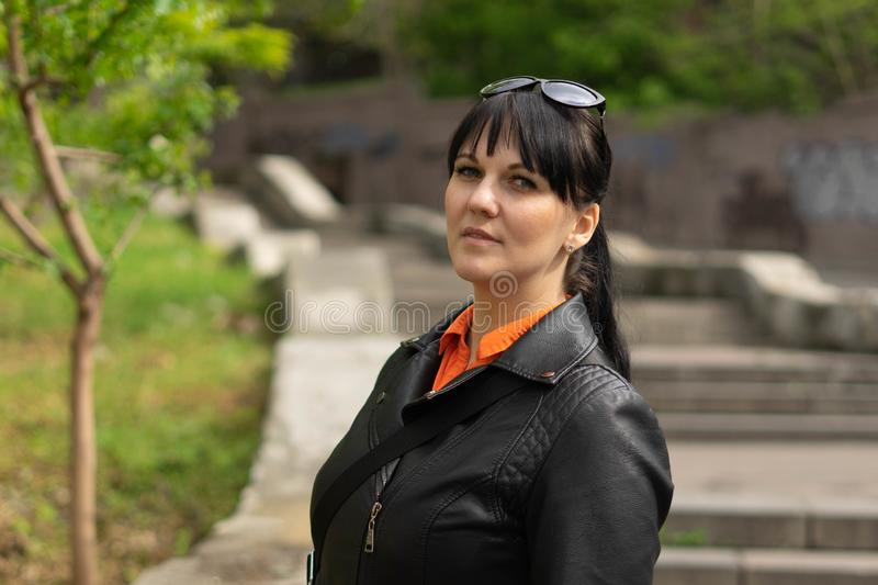 A beautiful brunette woman in a black jacket and an orange shirt is posing against the background of a long concrete staircase in stock photo