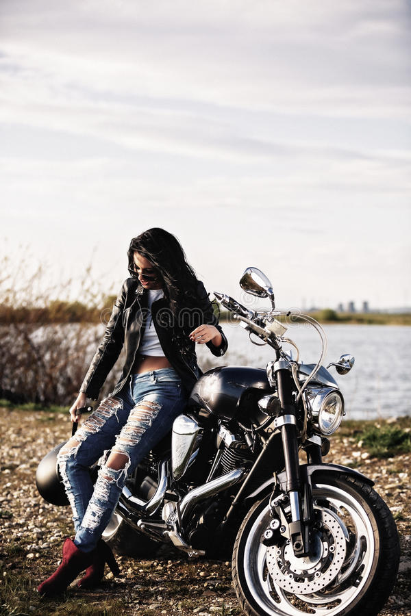 Beautiful brunette woman with a classic motorcycle c royalty free stock images
