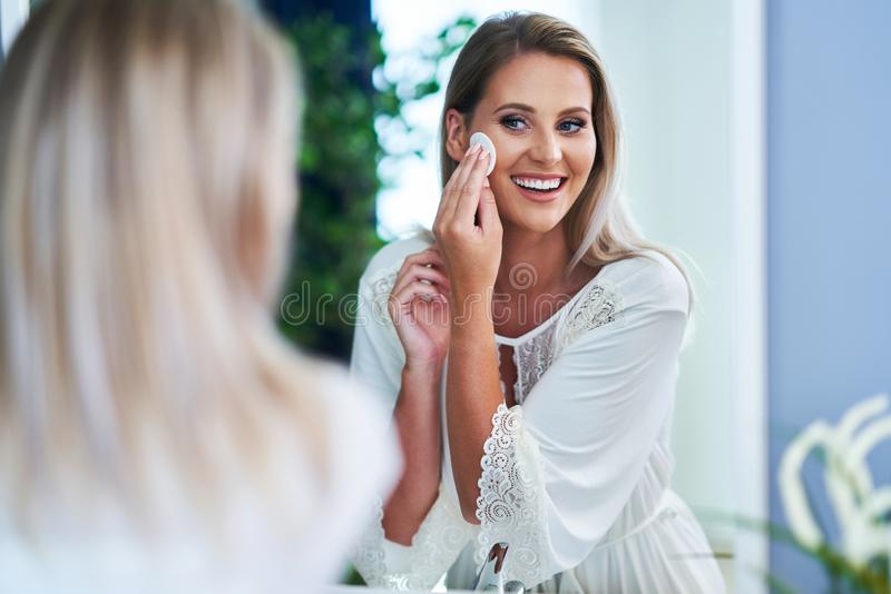 Beautiful brunette woman cleaning face in the bathroom. Picture of adult brunette woman in the bathroom stock photography