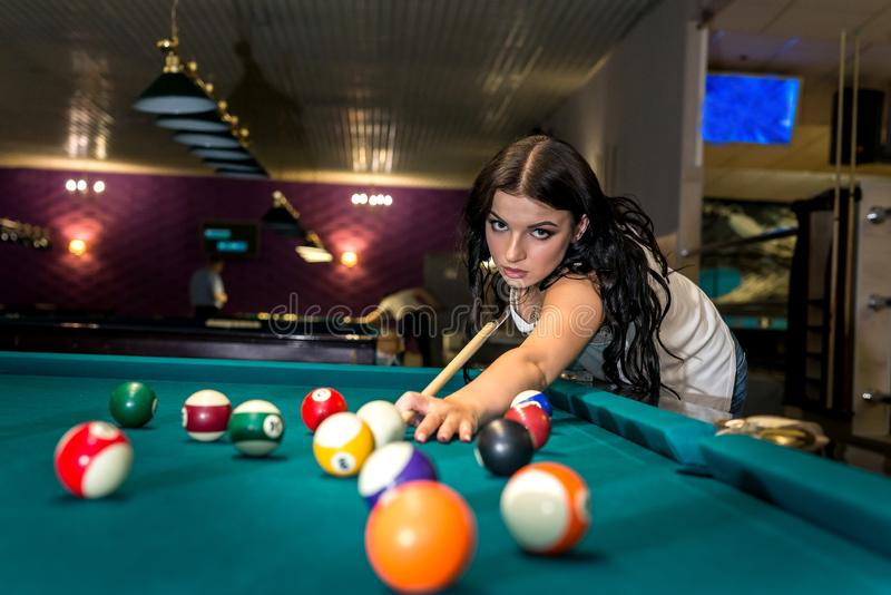 Beautiful brunette woman concentrated on billiard game stock image