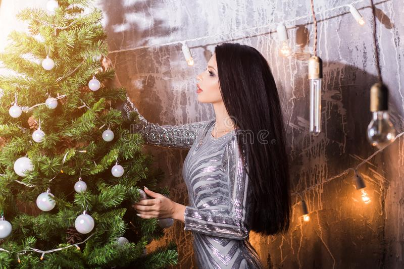 Beautiful brunette woman decorating a christmas tree at home in the living room stock photo