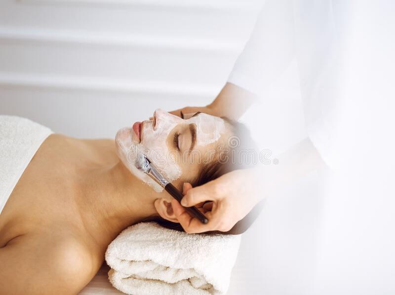 Beautiful brunette woman enjoying applying cosmetic mask with closed eyes. Relaxing treatment in medicine and spa center. Concepts stock photo