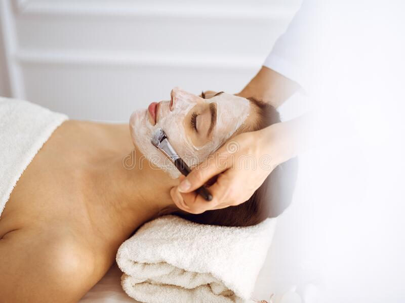 Beautiful brunette woman enjoying applying cosmetic mask with closed eyes. Relaxing treatment in medicine and spa center. Concepts royalty free stock images