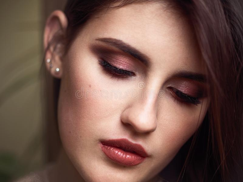 Beautiful brunette woman face closeup beauty eyes and lips makeup moody female portrait royalty free stock photography