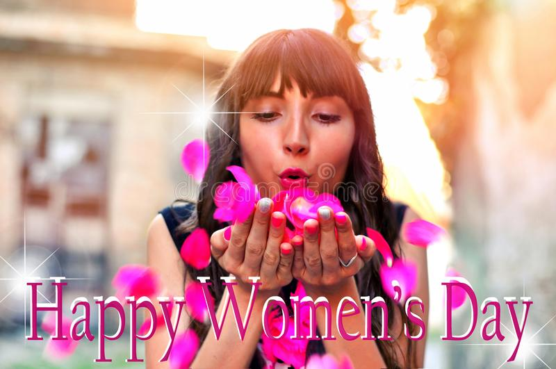Beautiful brunette woman with flowers blowing petals from her hands. Happy International Women`s Day text with blurred background royalty free stock image