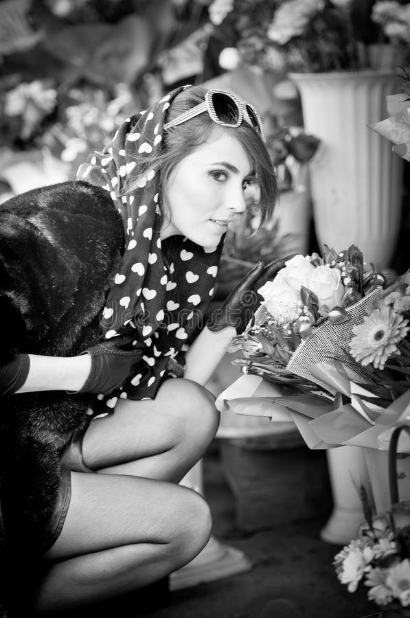 Beautiful brunette woman with gloves choosing flowers at the florist shop. Fashionable female with sunglasses and head scarf royalty free stock images
