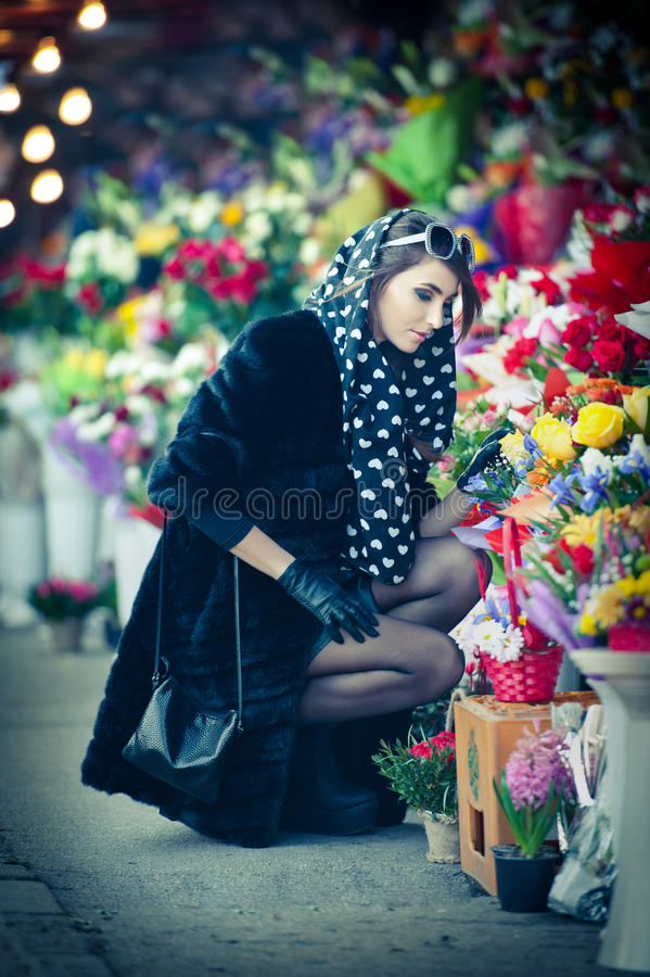 Beautiful brunette woman with gloves choosing flowers at the florist shop. Fashionable female with sunglasses and head scarf royalty free stock image