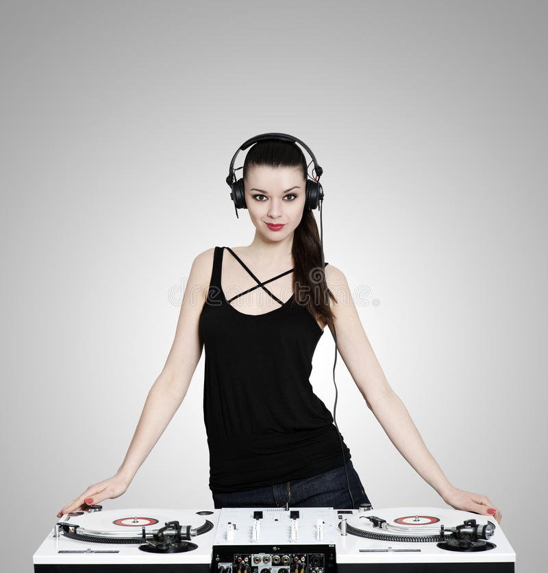 Beautiful brunette woman with headphones and turntables royalty free stock photos