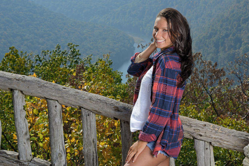 Beautiful brunette woman hiker stands at overlook stock image