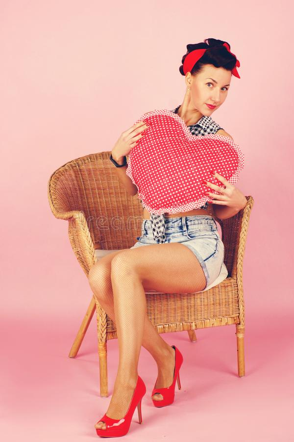 Beautiful brunette woman holding a plush heart, looking coquettishly, pin-up style on a pink background royalty free stock photography