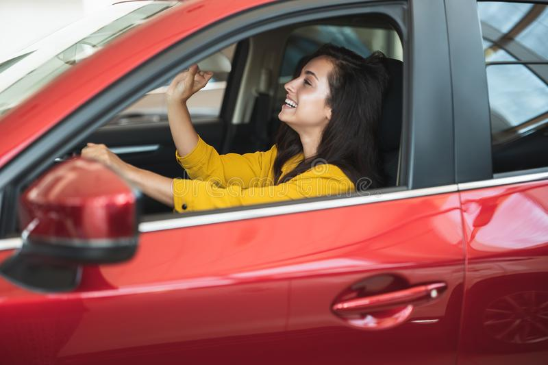 Beautiful brunette woman looking for new car in dealership center checking the interior royalty free stock image