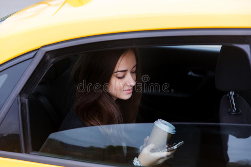 Beautiful brunette woman looking phone in taxi royalty free stock photography