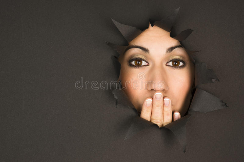 Beautiful Brunette Woman Looks Through Torn Hole Hand Covers royalty free stock photography