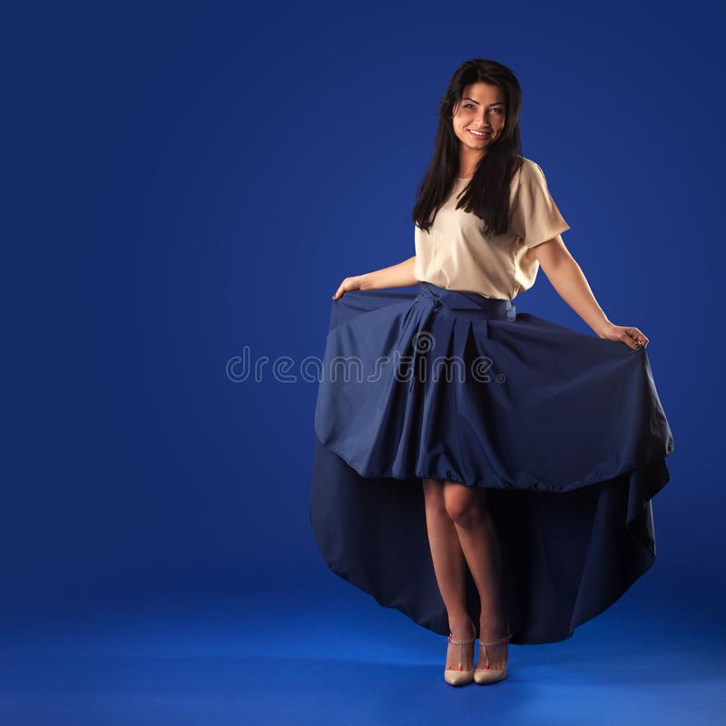 Woman in a lush long skirt posing on a blue studio background. Beautiful brunette woman in a lush long skirt posing on a blue studio background royalty free stock images