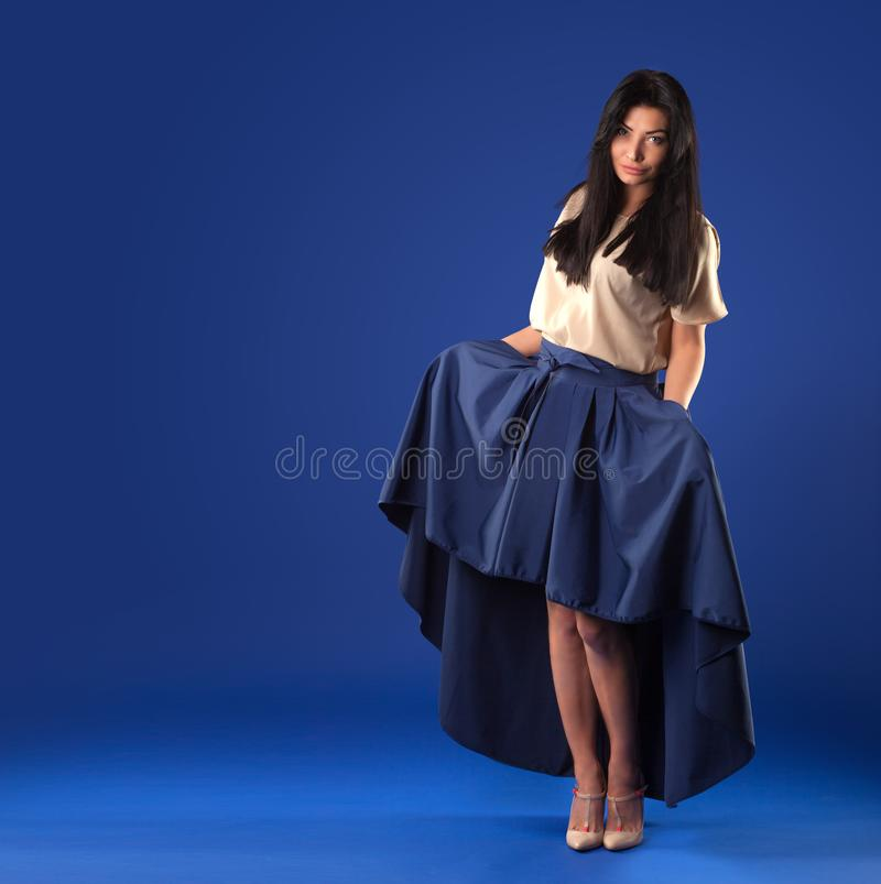 Woman in a lush long skirt posing on a blue studio background. Beautiful brunette woman in a lush long skirt posing on a blue studio background stock photos