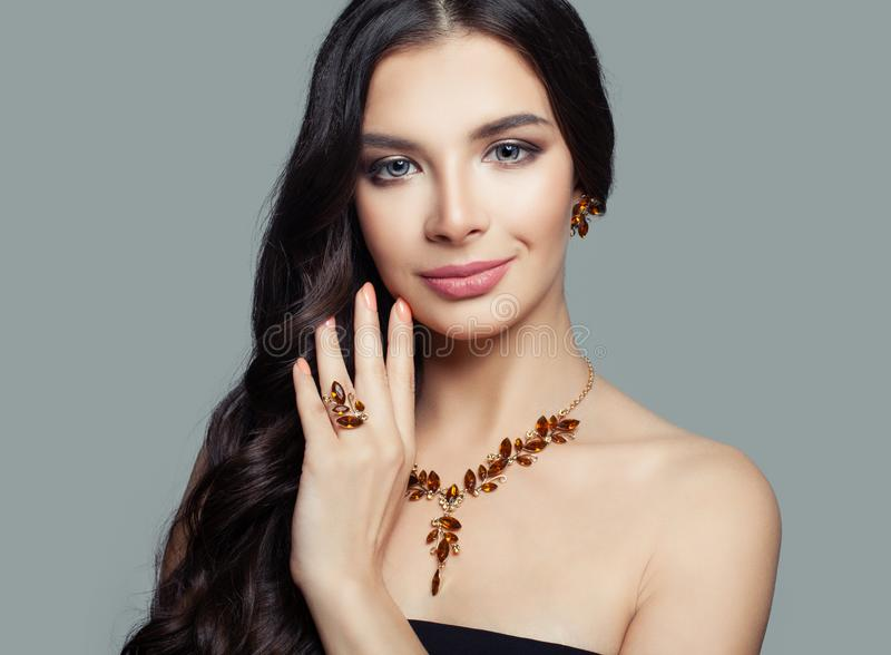 Beautiful brunette woman with makeup and amber ring, necklace and earrings stock photography