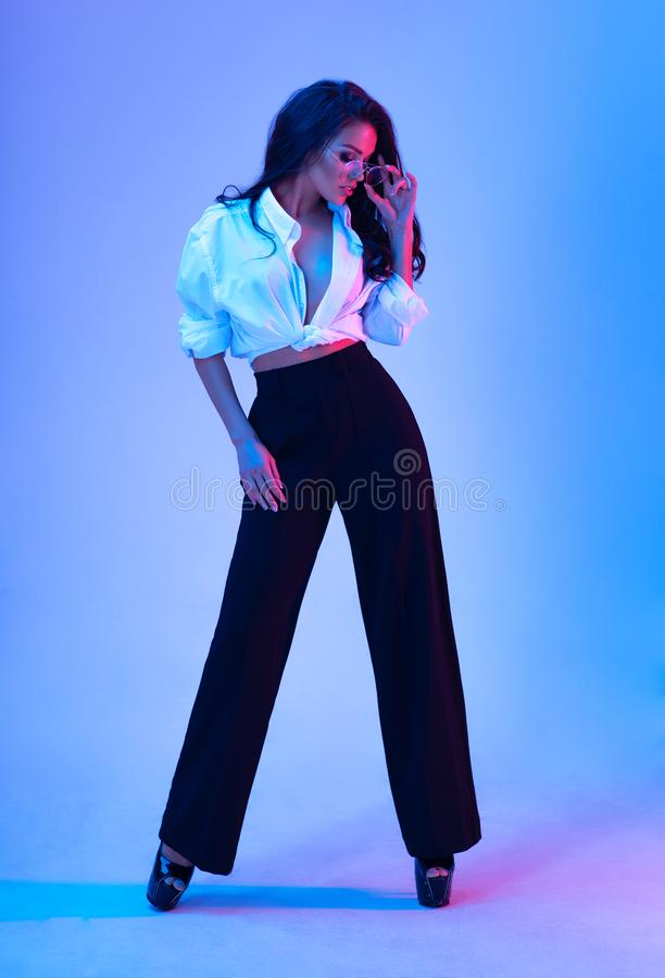 Beautiful brunette woman with makeup wearing white shirt and black trousers stock photos