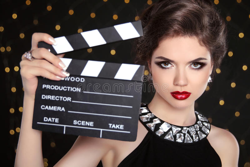 Beautiful brunette woman model holding film clap board cinema. Fashion portrait of girl with makeup, hairstyle and expensive jewelry royalty free stock image