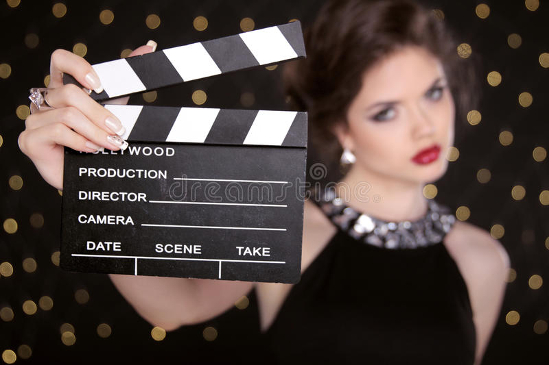 Beautiful brunette woman model holding film clap board cinema. Fashion portrait of girl with makeup, hairstyle and expensive jewelry stock photo