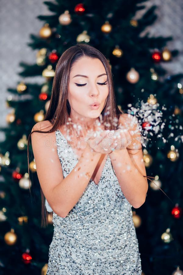 Beautiful brunette woman in new year silver dress blowing snow with hands on Christmas tree background royalty free stock image
