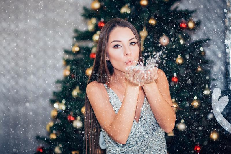 Beautiful brunette woman in new year silver dress blowing snow with hands on Christmas tree background. Holiday, New year, royalty free stock photos