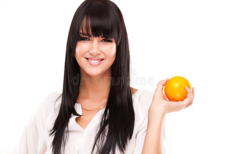 Beautiful brunette woman with orange on white background stock photos