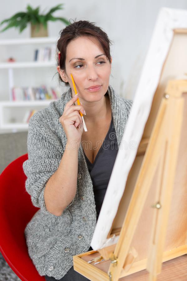 Beautiful brunette woman painting on canva royalty free stock image