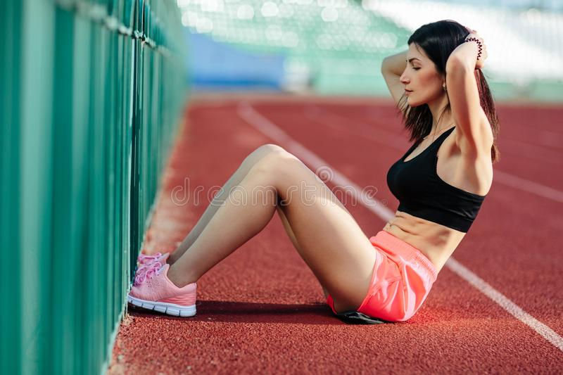 Beautiful brunette woman in pink shorts and tank top does exercises with press at the stadium.  stock photos