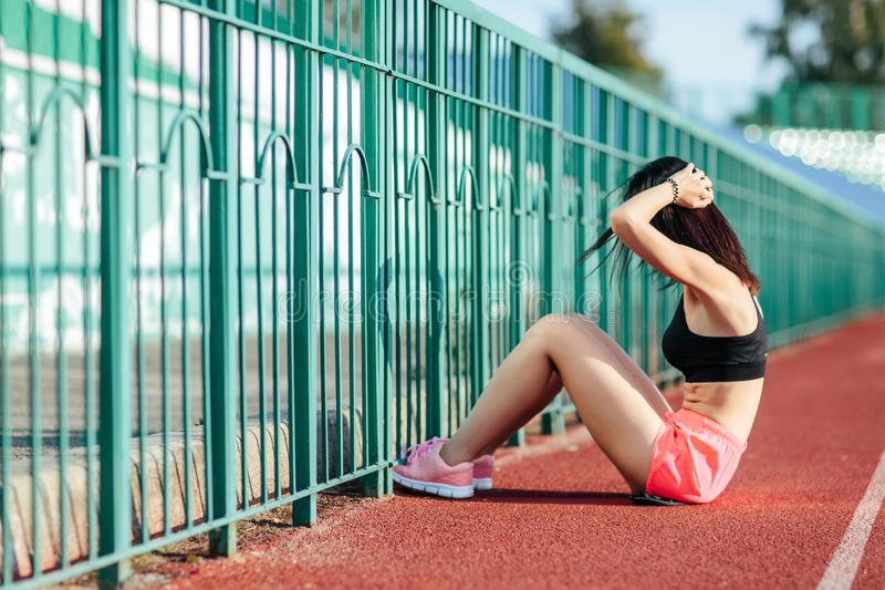 Beautiful brunette woman in pink shorts and tank top does exercises with press at the stadium. Beautiful girl does exercises with press at the stadium stock photo