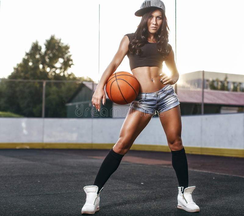 Beautiful brunette woman playing basketball on court outdoor. Sunset. Fitness girl with basketball ball playing game outdoor stock photo