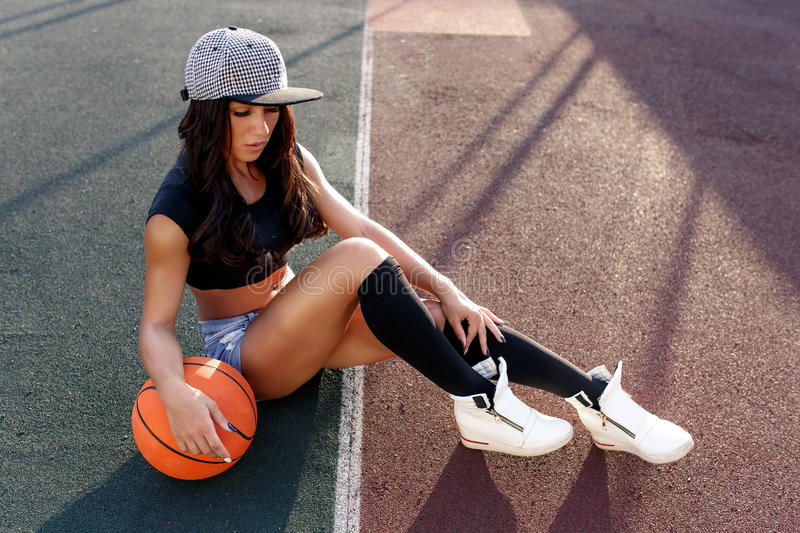 Beautiful brunette woman playing basketball on court outdoor. Sunset. Fitness girl with basketball ball playing game outdoor stock photography