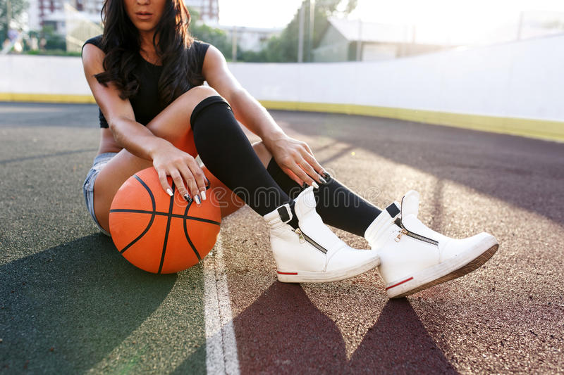 Beautiful brunette woman playing basketball on court outdoor stock photos