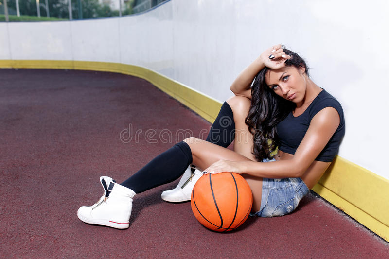 Beautiful brunette woman playing basketball on court outdoor. Sunset. Fitness girl with basketball ball playing game outdoor royalty free stock photos