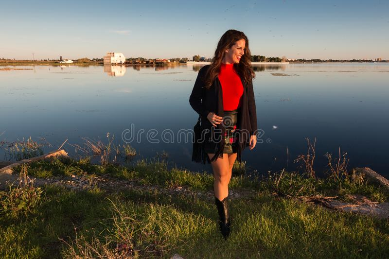 Beautiful brunette woman portrait standing outside in a sunny day, with a lake in background stock photos