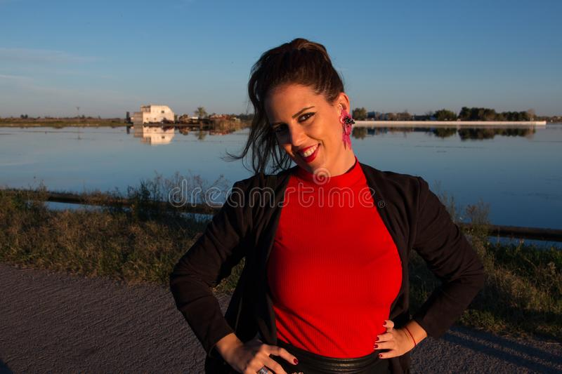 Beautiful brunette woman portrait standing outside in a sunny day, with a lake in background stock images