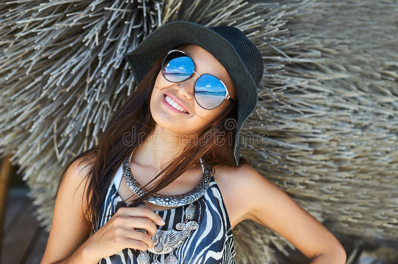 Beautiful brunette woman posing at sunny summer day close up portrait. Girl wearing fashionable sunglasses and hat stock image