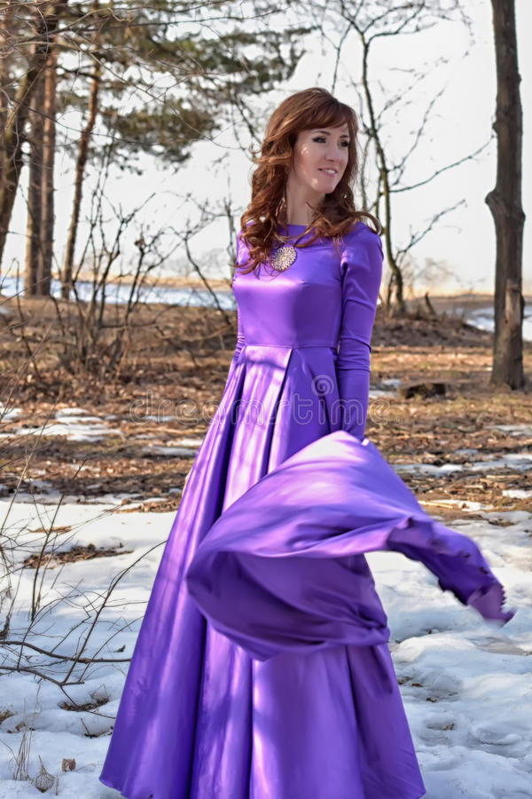 Beautiful brunette woman in purple long dress. In the forest in winter royalty free stock photo