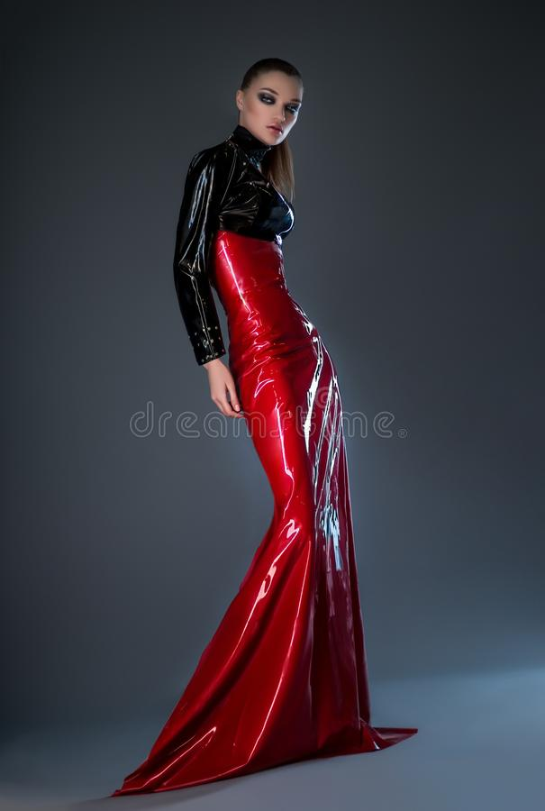 Beautiful brunette woman in red and black latex dress. Posing at camera against dark background stock image