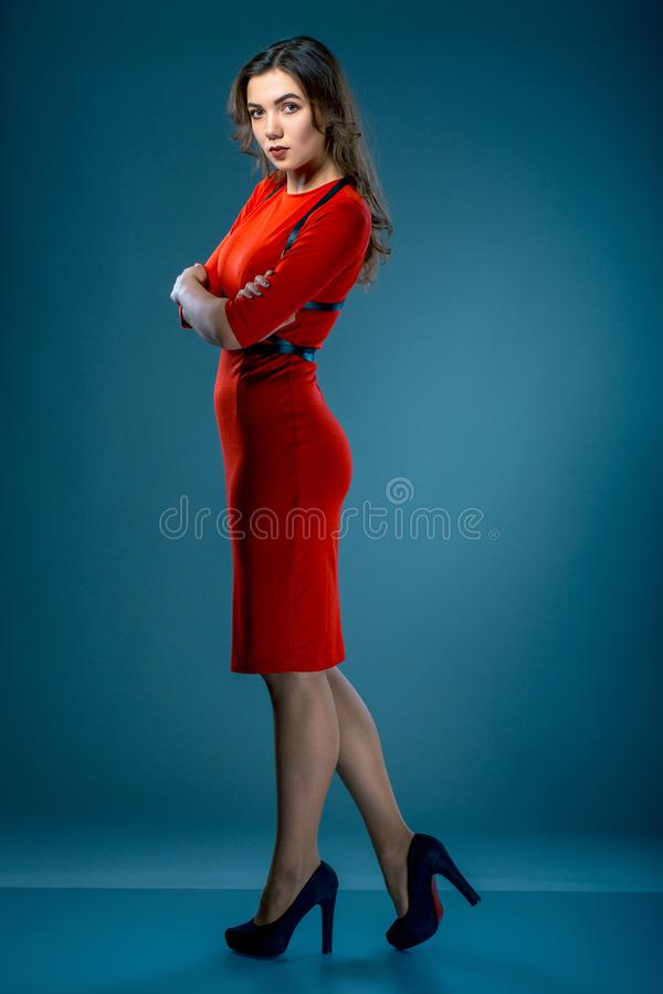 Beautiful brunette woman in red dress with belts is posing in studio over grey blue background royalty free stock photography